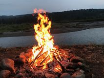 Campfire in front of river Royalty Free Stock Photography