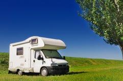 Campista estacionado em um campo Fotos de Stock Royalty Free