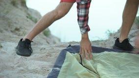 Campista que põe acima da barraca, preparando-se a durante a noite no turismo selvagem, verde, caminhando video estoque