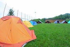Campistas do escuteiro das barracas em um prado verde fotos de stock