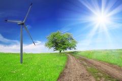 Campo, árbol, cielo azul con la turbina de viento Imagen de archivo