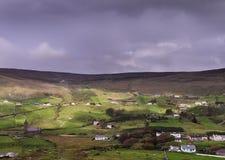 Campo agrícola irlandés con las casas tradicionales en la ladera Fotografía de archivo