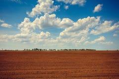 Campo arabile con il cielo nuvoloso ed il sole Fotografia Stock