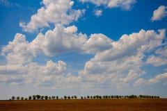 Campo arabile con il cielo nuvoloso ed il sole Immagine Stock Libera da Diritti