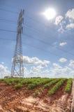 Campo arato al sole con il palo di potenza Immagine Stock