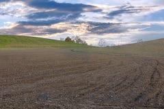 campo arato coltivato al crepuscolo sotto il cielo nuvoloso Fotografie Stock