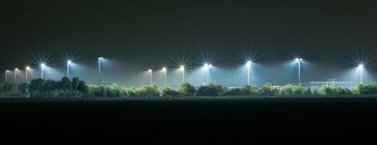 Campo atlético iluminado por las luces brillantes en la oscuridad imagen de archivo