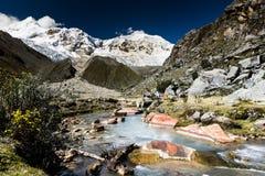 Campo base nel BLANCA di Cordigliera con le montagne innevate e una torrente montano Fotografia Stock Libera da Diritti