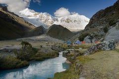 Campo base nel BLANCA di Cordigliera con le montagne innevate e una torrente montano Fotografie Stock