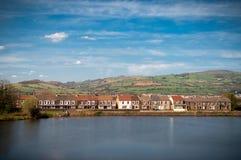 Campo británico con las casas, las colinas y el lago Imagen de archivo