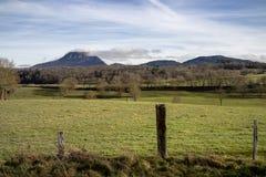 Campo com vista no vulcão de Puy de Dome D'Auvergne dos volcans do DES de Parc Fotos de Stock Royalty Free