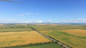 Campo con el pueblo, camino, tierras de labrantío en el día soleado claro, vídeo aéreo almacen de metraje de vídeo