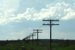 Campo con le colonne di electrity Fotografia Stock