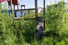 Campo da giuoco abbandonato con la scalata del bambino dell'oscillazione soleggiata, Fotografia Stock
