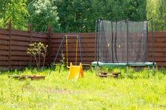 Campo da giuoco dei bambini con il trampolino e le oscillazioni fotografie stock libere da diritti