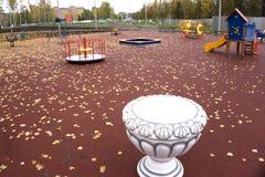 Campo da giuoco dei bambini nel giallo del tubo degli alberi del parco fotografia stock