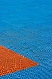 Campo da giuoco di plastica blu ed arancio di struttura con le tracce su  fotografia stock