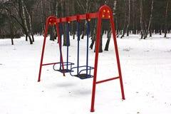 Campo da giuoco nell'inverno Il campo da gioco per bambini nella neve Oscillazione del ` s dei bambini fotografia stock libera da diritti