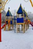 Campo da giuoco vuoto dei bambini nel parco della città di inverno Immagini Stock Libere da Diritti