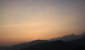 Campo da montanha durante a paisagem natural do por do sol Fotos de Stock