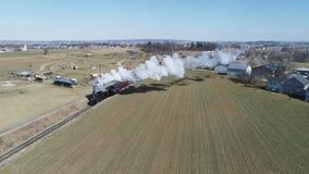 Campo de Amish con el tren de pasajeros del vapor que sopla a través en un invierno D metrajes