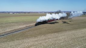 Campo de Amish con el tren de pasajeros del vapor que sopla a trav?s en un invierno D almacen de video
