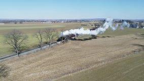 Campo de Amish con el tren de pasajeros del vapor que sopla a trav?s en un invierno D metrajes