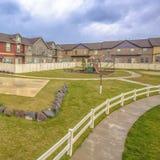 Campo de básquete do quadro e campo de jogos quadrado com casas e céu nebuloso no fundo foto de stock