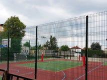 Campo de básquete moderno no pátio da escola primária Campo de jogos multifuncional do ` s das crianças com o artificial surgido  Fotos de Stock Royalty Free