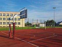 Campo de básquete moderno no pátio da escola primária Campo de jogos multifuncional do ` s das crianças com o artificial surgido  Imagem de Stock