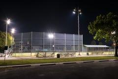 Campo de béisbol vacío con las luces encendido en la noche Imagen de archivo libre de regalías