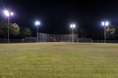 Campo de béisbol vacío en la noche con las luces encendido Foto de archivo libre de regalías