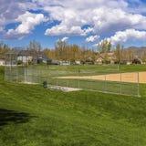 Campo de basebol quadrado do quadro com vista da montanha e do céu azul nebuloso em um dia ensolarado fotos de stock royalty free