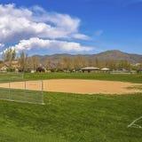Campo de basebol quadrado do quadro com vista da montanha e do céu azul nebuloso em um dia ensolarado fotografia de stock