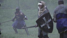 Campo de batalla ahumado de edades medievales, gente en armadura con las armas almacen de metraje de vídeo