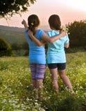 Campo de duas flores das meninas no por do sol Imagem de Stock