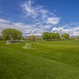 Campo de esportes vasto do quadrado com a bancada da rede e do basebol do objetivo do futebol atrás de uma cerca fotos de stock