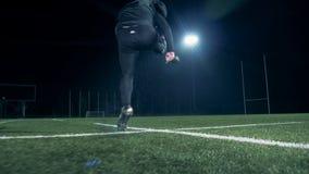 Campo de fútbol americano con un jugador del rugbi que golpea la bola almacen de metraje de vídeo