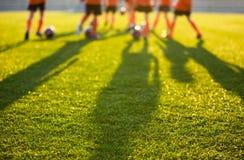 Campo de fútbol borroso en la escuela Entrenamiento joven de los jugadores de fútbol imagen de archivo libre de regalías