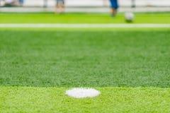 Campo de fútbol con los niños que juegan en el foco selectivo del extremo lejano Fotos de archivo libres de regalías