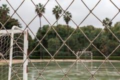 Campo de fútbol mojado visto a través de red Fotos de archivo
