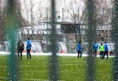 Campo de fútbol Nevado en diciembre, helada y tiempo frío Fútbol del juego de la gente joven Foco selectivo Foto de archivo libre de regalías