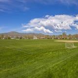 Campo de futebol quadrado do quadro e campo de basebol com vista da montanha e do céu azul nebuloso imagem de stock