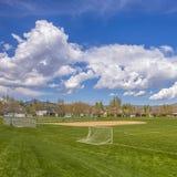 Campo de futebol quadrado e campo de basebol com vista da montanha e do céu azul nebuloso imagem de stock royalty free