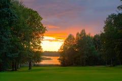 Campo de golf de la orilla del lago en la puesta del sol Fotos de archivo libres de regalías