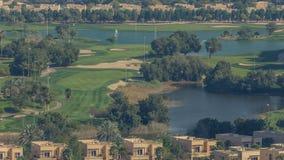 Campo de golf hermoso cerca de rascacielos modernos del timelapse del puerto deportivo de Dubai en la ciudad de lujo de Dubai, Un almacen de video