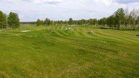 Campo de golf de la visión aérea Golfistas que caminan abajo del espacio abierto en un curso con la bolsa de golf y la carretilla Imagenes de archivo