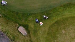 Campo de golf de la visión aérea Golfistas que caminan abajo del espacio abierto en un curso con la bolsa de golf y la carretilla Foto de archivo libre de regalías