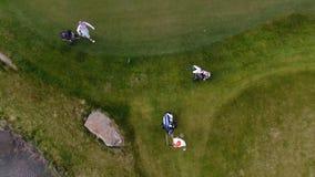 Campo de golf de la visión aérea Golfistas que caminan abajo del espacio abierto en un curso con la bolsa de golf y la carretilla Fotografía de archivo libre de regalías