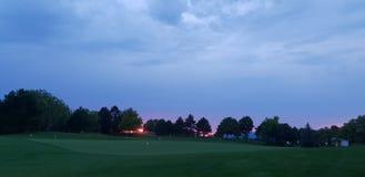 Campo de golf y puesta del sol n el backround foto de archivo libre de regalías